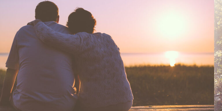 Couple sitting on bench watching sunset